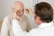 an optician fitting eyeglasses on an elderly patient