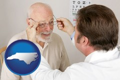 north-carolina map icon and an optician fitting eyeglasses on an elderly patient