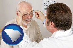 south-carolina an optician fitting eyeglasses on an elderly patient