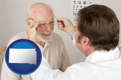 south-dakota map icon and an optician fitting eyeglasses on an elderly patient